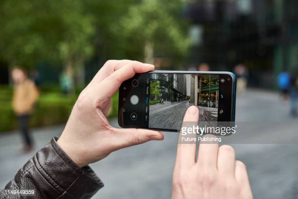 Detail of a man taking photographs with an Honor 20 Pro smartphone around Southwark area of London on June 4 2019