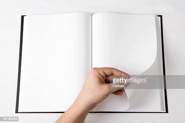 detail of a man turning a page of a blank book - category:pages stock pictures, royalty-free photos & images