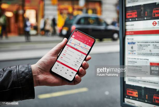 Detail of a man waiting at a bus stop while holding an Honor 20 Pro smartphone with a bus timetable app visible on screen, on June 4, 2019.