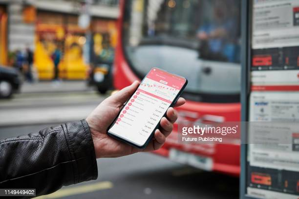 Detail of a man waiting at a bus stop while holding an Honor 20 Pro smartphone with a bus timetable app visible on screen on June 4 2019