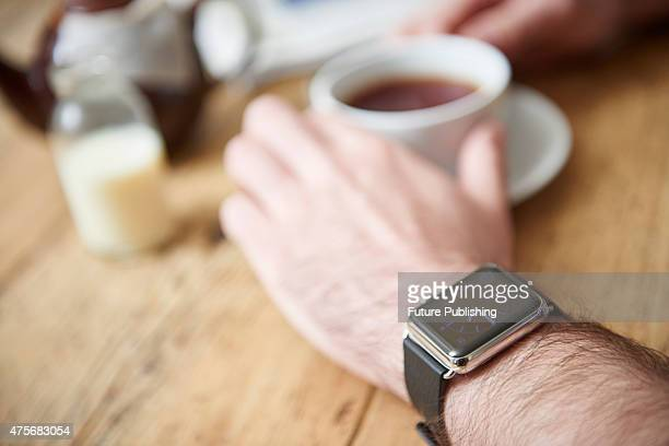 Detail of a man wearing an Apple Watch while sitting inside a cafe taken on May 21 2015