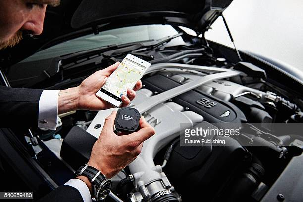Detail of a man with a Sony Xperia Z5 Spectreedition smartphone and Streetwise GPS Tracker photographed with an Aston Martin Vanquish Volante taken...