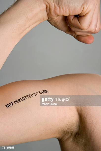 Detail of a man's bicep stamped 'Not permitted to work'