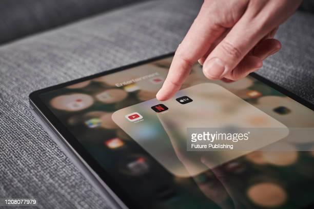 Detail of a mans hand pressing the Netflix app icon on an Apple iPad Pro tablet, taken on March 6, 2020.