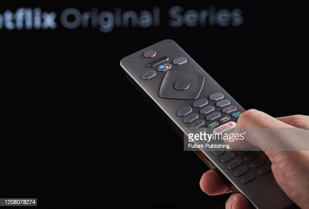 Detail of a mans hand pressing the Netflix button on a TV remote control with Netflix streaming on a television in the background taken on March 6...
