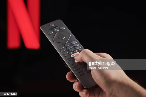 Detail of a mans hand pressing the Netflix button on a TV remote control, with Netflix streaming on a television in the background, taken on March 6,...