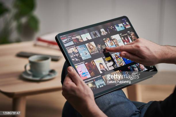 Detail of a mans hand scrolling through Netflix on an Apple iPad Pro, taken on March 6, 2020.