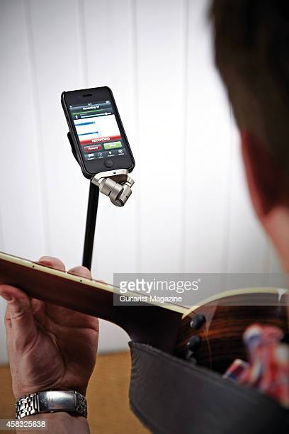 Detail of a musician playing an acoustic guitar in front of an Apple iPhone 4S and Rode iXY stereo mic, taken on November 26, 2013.