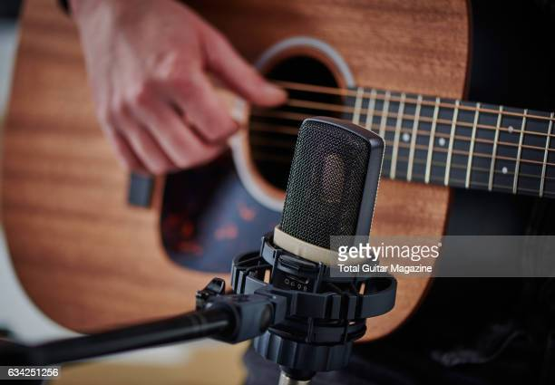 Detail of a musician playing an acoustic guitar next to an AKG C314 condenser microphone for a feature on recording your own music, taken on April...