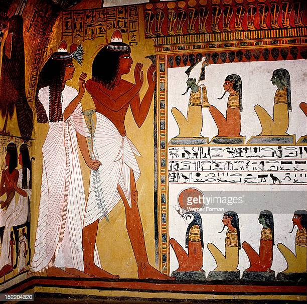 A detail of a painting in the tomb of Sennedjem The tomb owner and his wife pay homage before a shrine of Osiris Horus and the other gods of the...