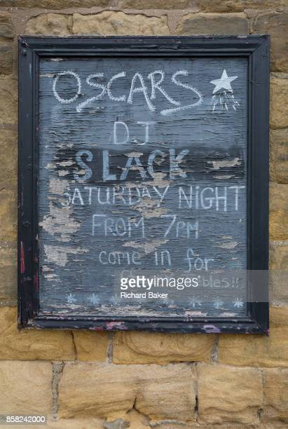 Detail of a peeling and faded pub sign feating its Saturday night entertainment in a Northumbrian town on 26th September 2017 in Alnwick...