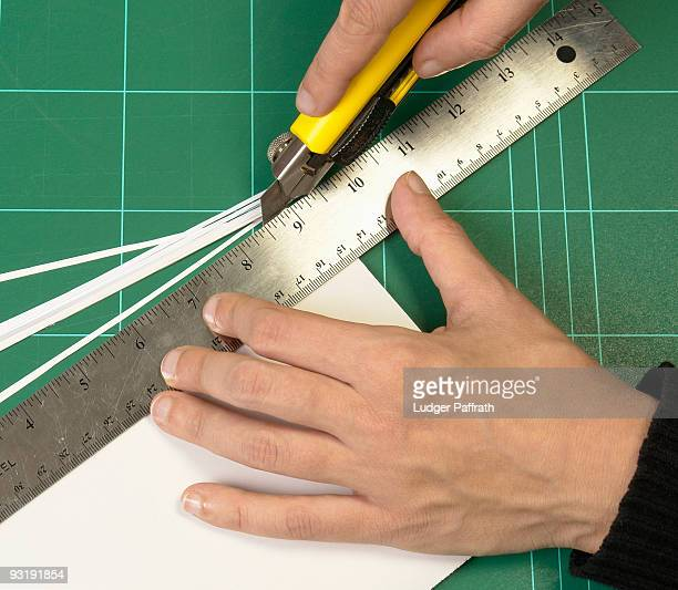 detail of a person cutting paper - utility knife stock photos and pictures