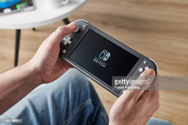 Detail of a person holding and playing a 2019 Nintendo Switch Lite handheld video games console with a Gray finish taken on November 7 2019
