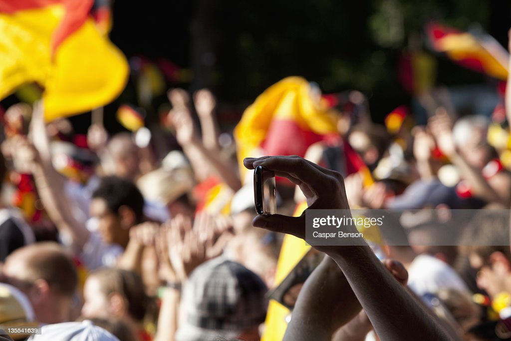 Detail of a person in a crowd holding a mobile phone : Stock Photo