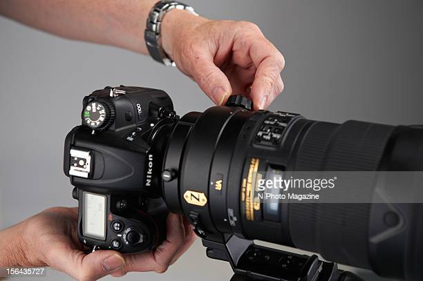 Detail of a photographer adjusting a Nikon D800 with a 300mm f/28 AFS VR lens taken on April 13 2012
