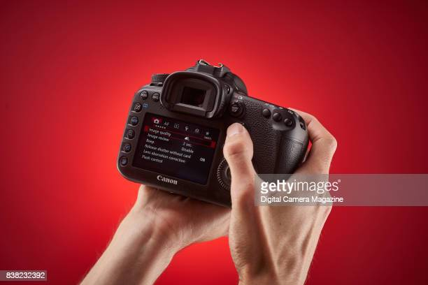 Detail of a photographer holding a Canon 7D Mk II digital SLR camera with the LCD screen menu visible taken on August 16 2016