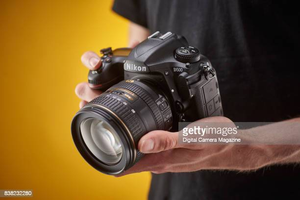 Detail of a photographer holding a Nikon D500 digital SLR camera taken on August 16 2016