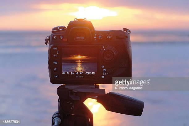 Detail of a tripod-mounted Nikon DSLR camera set up to take pictures of a coastal sunset, taken on July 19, 2014.