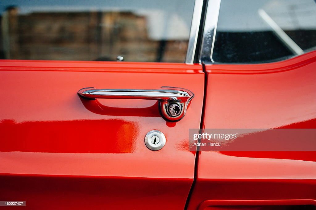 Detail of a vintage red car door handle : Stock Photo