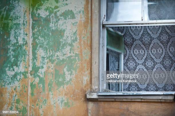 A detail of a vintage soviet era building exterior with peeling paint texture.
