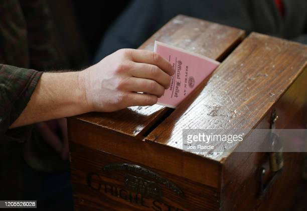 Detail of a voter dropping a voting ballot into the ballot box at the Town Hall on February 11 2020 in Chichester New Hampshire Voters are casting...