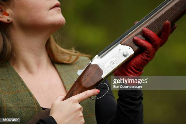 Detail of a woman and her rifle during at clay pigeon shoot