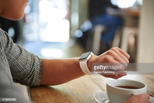 Detail of a woman checking an Apple Watch Sport while sitting inside a cafe, taken on May 21, 2015.