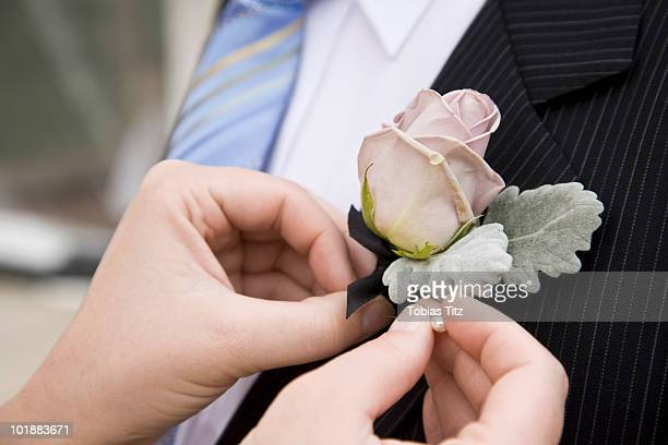 detail of a woman pinning a corsage to a jacket lapel,  melbourne, victoria, australia - prom stock pictures, royalty-free photos & images