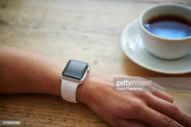 Detail of a woman wearing an Apple Watch Sport while sitting inside a cafe taken on May 21 2015