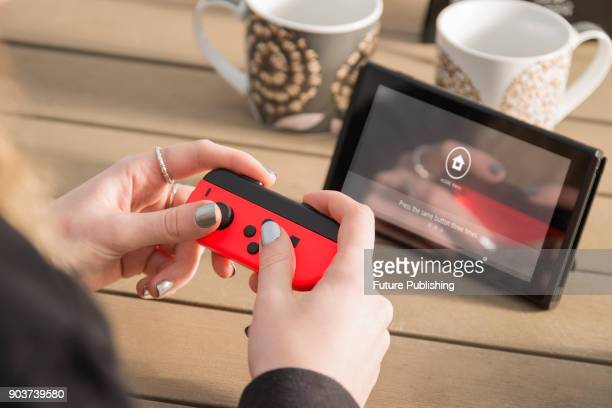 Detail of a young woman playing video games on a Nintendo Switch home console with a Joy Con wireless controller taken on March 7 2017