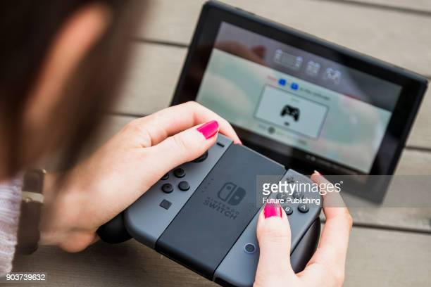 Detail of a young woman playing video games on a Nintendo Switch home console with a pair Joy Con wireless controllers attached to a Joy Con Grip...