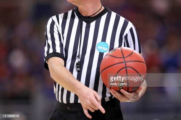 A detail of an NCAA referee holding an official wilson NCAA tournament basketball as the North Carolina State Wolfpack play against the Kansas...