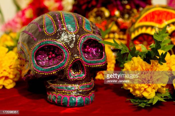 CONTENT] Detail of an ornamental skull resting on red velvet surrounded by marigolds at a Dia de los Muertos exhibition Walker's Point Center for the...