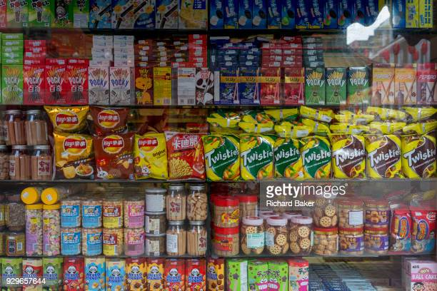 A detail of assorted snacks including biscuits crisps and other merchandise on shelves in a corner shop window on Gerrard Street Chinatown on 5th...