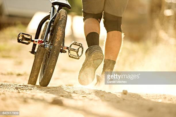 Detail of BMX wheel and man's shoes kicking dirt.