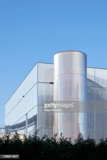 Detail of box-like polished stainless-steel facade with cylindrical stairwell. MK Gallery, Milton Keynes, United Kingdom. Architect: 6a Architects,...