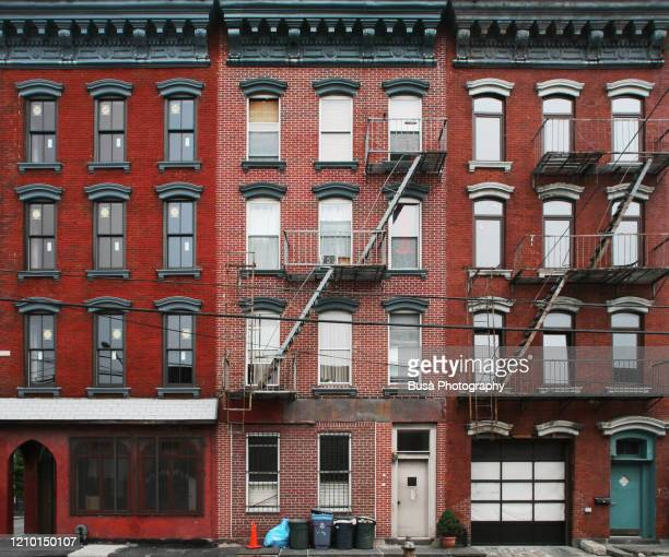 detail of brick facades of traditional walk-ups in new york city with rusty fire escapes. new york city, usa - new york city stock pictures, royalty-free photos & images