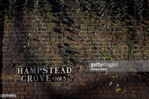 Detail of brick wall with Hampstead Grove NW3 road sign Hampstead Grove is a street in London's Hampstead District Camden with exclusive houses of...