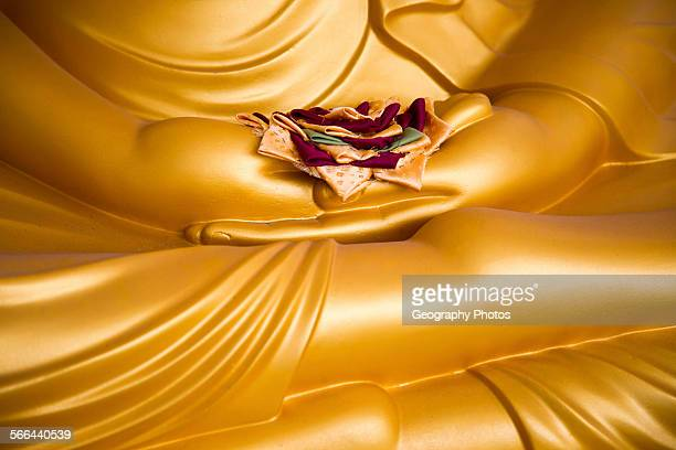 Detail of Buddha statue with offering in palm of hands Gangaramaya Temple Colombo Sri Lanka