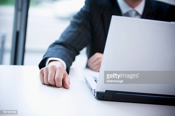 detail of businessman at desk with laptop computer
