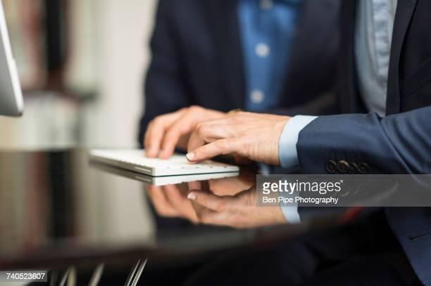 Detail of businessmans hands typing on desktop computer keyboard