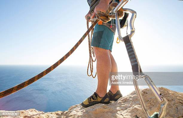 Detail of climber's legs on cliff, high above sea