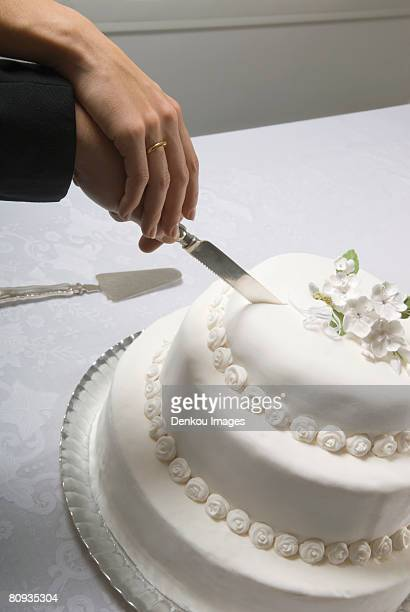 Detail of couple's hands cutting wedding cake