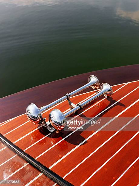 Detail of dual chrome trumpet horn on wooden boat floating in water.