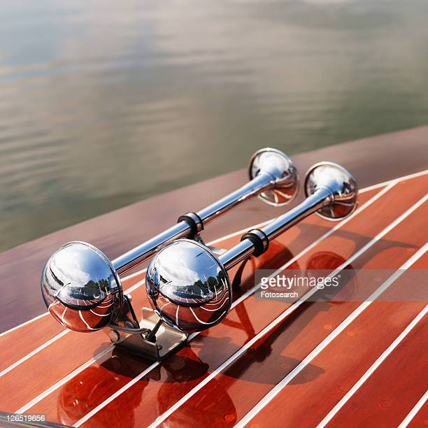 Detail of dual chrome trumpet horns on wooden boat floating in water.