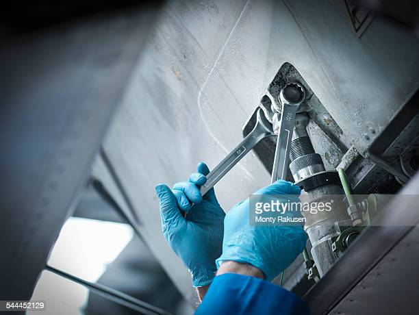 Detail of engineer using spanner in aircraft maintenance factory, close up