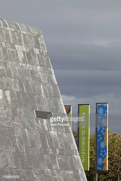 Detail of exterior of main building showing dark grey Barents Blue gneiss cladding and autumnal foliage against stormy sky Norwegian Petroleum Museum...
