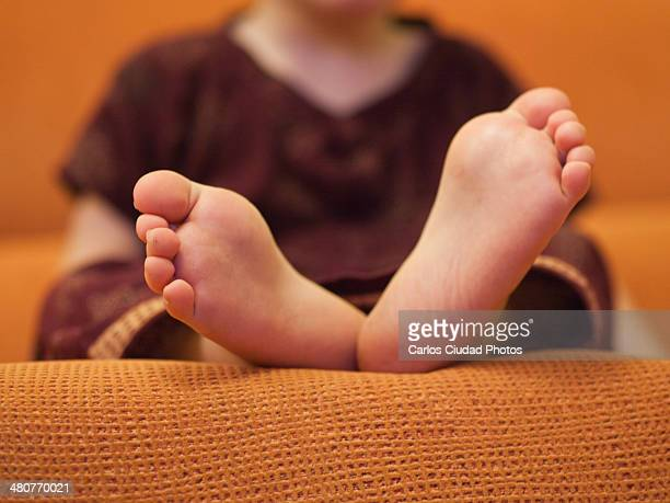 Detail of feet of a child sitting on the sofa