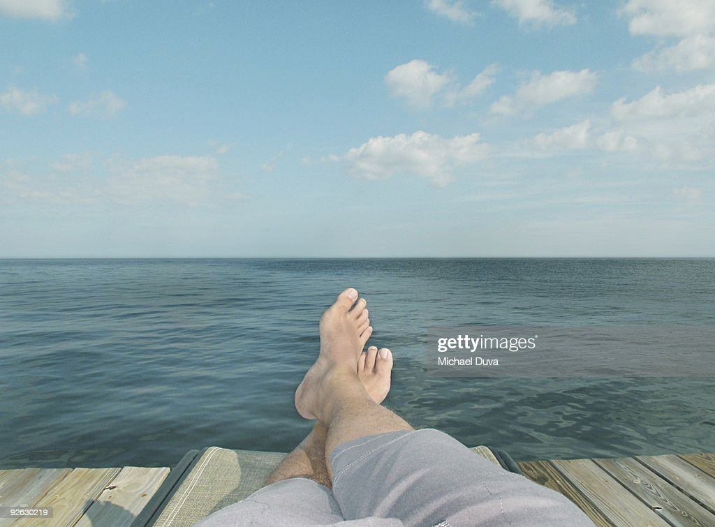 detail of feet relaxing on chair in front of water : Stock Photo