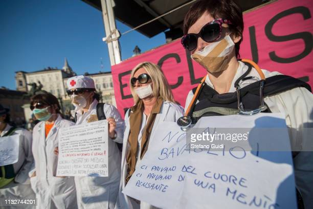 Detail of four women dressed as nurses holding protest signs during the No Vax demonstration against mandatory vaccines The No Vax procession with...